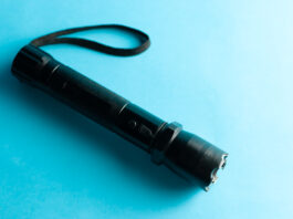 A black metal flashlight with shocker at the blue background. protection and security concept. for design and decoration.
