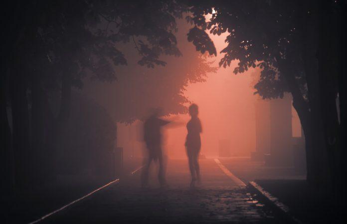 Ein Wahnsinniger oder Verbrecher greift ein Opfer auf einer schrecklichen, nächtlichen Straße an.