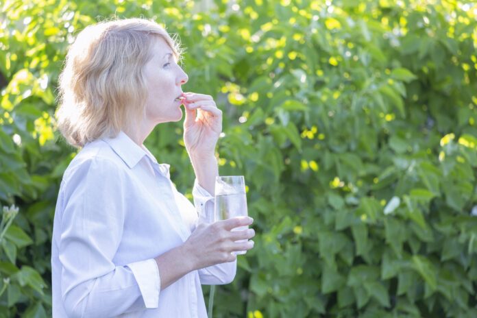A woman takes a pill washed down with water from a glass in the early morning against a background of greenery