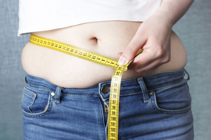 A woman's hand measure her stomach with a tape measures, overweight concept