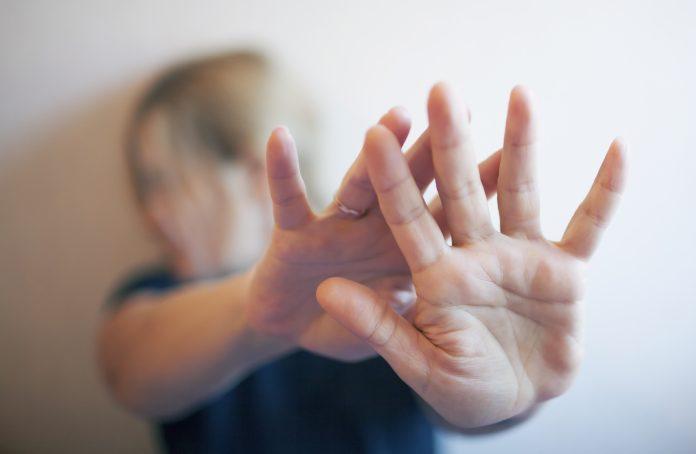 Een jonge vrouw beschermt zichzelf met de hand
