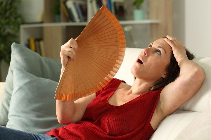 Femme adulte ventilée souffrant d'un coup de chaleur, assise dans le salon à la maison
