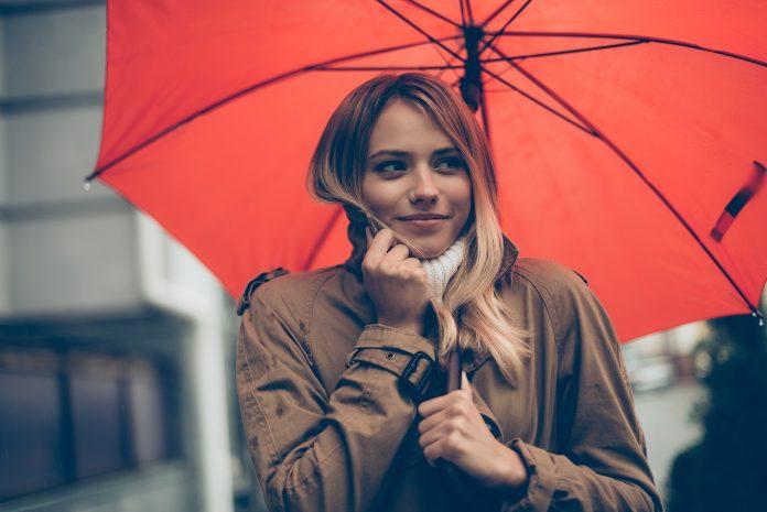 Attraktive junge lächelnde Frau, die einen Regenschirm trägt und ihren Mantel anpasst, während sie durch die Straße geht