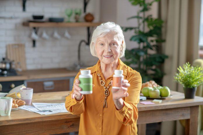 Gesund sein. Grauhaarige, gut aussehende Frau zeigt zwei Gläser mit Vitaminen