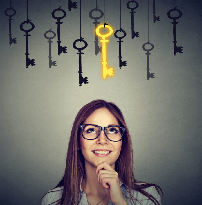 Beautiful thoughtful woman looking upSmiling woman looking up at vintage golden key to success among many others hanging. Concept of business aspirations, achievement