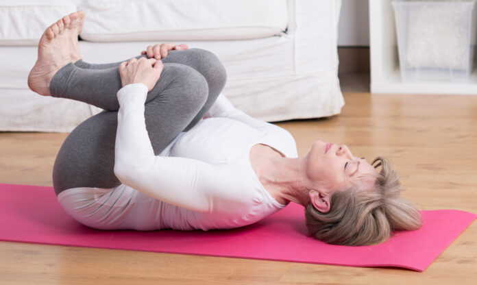Beauty mature woman practicing pilates at home