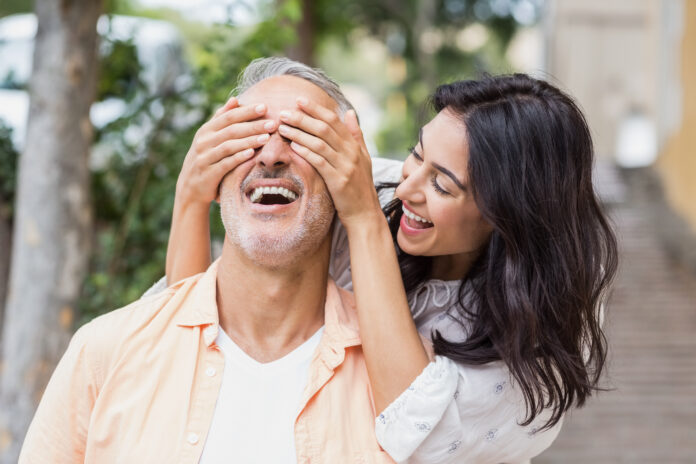 Cheerful woman covering eyes of man in city