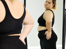 Chubby woman standing and looking at her stomach in a mirror.