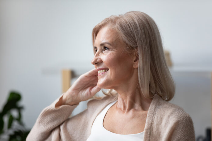 Close up of positive elderly female pensioner sit relax at home look in distance window dreaming or visualizing, smiling mature woman grandmother lost in thoughts remember good old days, happy life