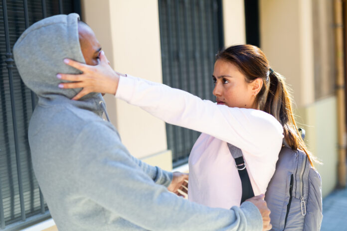 Determined young Latina using Krav Maga techniques to protect herself from attacker man on city street. Female self-defense concept