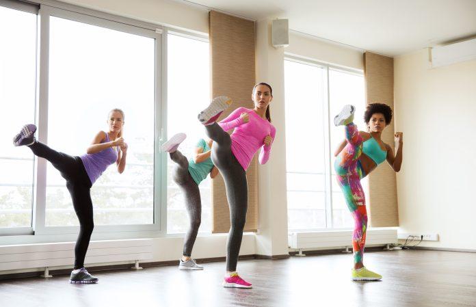 concept de fitness, de sport, d'entraînement, de gymnase et d'arts martiaux - groupe de femmes s'entraînant à la technique de combat dans un gymnase