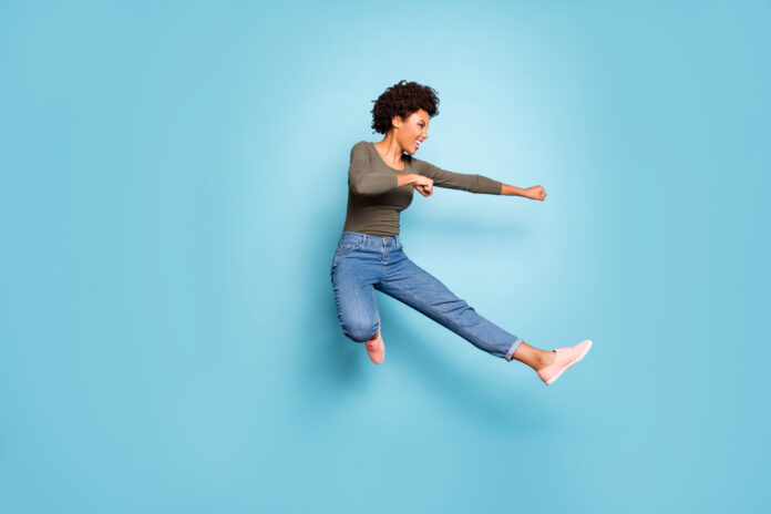 Full length photo of dark skin wavy lady jumping high dancing modern, youngster moves practicing judo fighting wear casual outfit isolated pastel blue color background