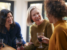 Grupo de amigas maduras que se reúnen en casa para hablar y beber vino juntas