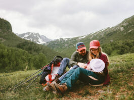 Happy family hiking with baby in mountains travel vacation outdoor mother and father parents lifestyle summer trip together