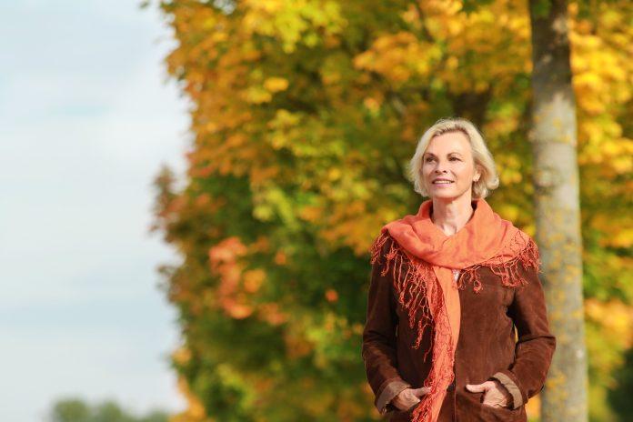 De gelukkige rijpe vrouw voor gouden herfstbladeren geniet van vrije tijd