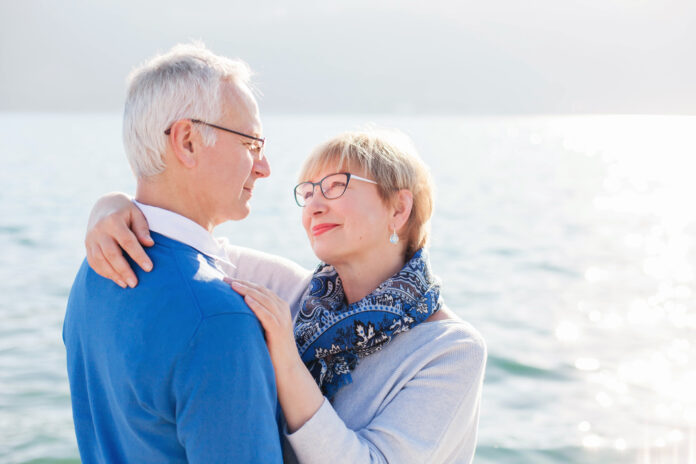 Happy senior couple at sea beach outdoor. Man and woman are hugging, embracing, enjoying retirement and life. Concept of wellbeing, happiness, male and female health, lifestyle moments.