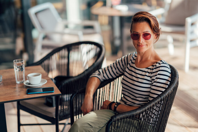 Happy woman wearing stripe shirt and sunglasses sitting in the cafe