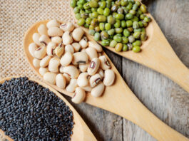 Healthy diet beans. Healthy food with soybean and mung bean and sesame seeds in wooden spoons on hemp sack and wooden desk background. Nutritious diet and above view of beans.