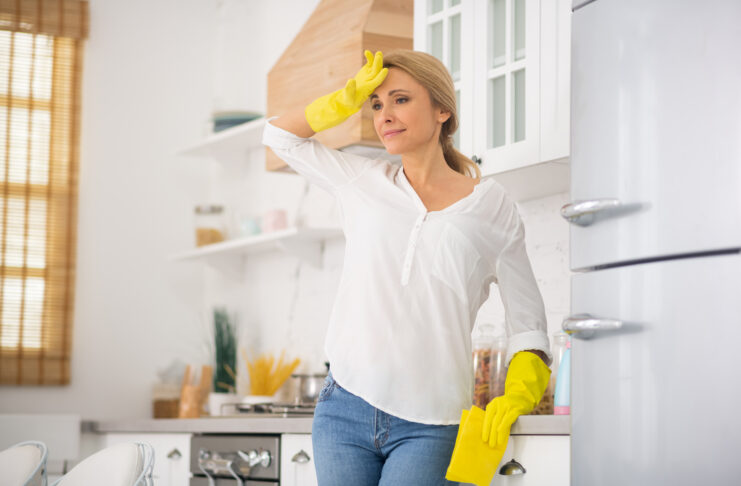 Hot flash. Blonde housewife in protective gloves feeling bad
