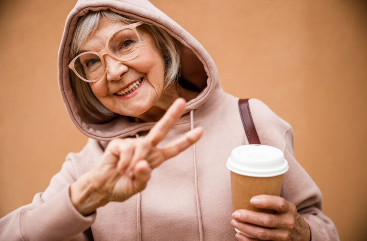 Jolly aged female in hood and glasses is demonstrating peace gesture while drinking coffee