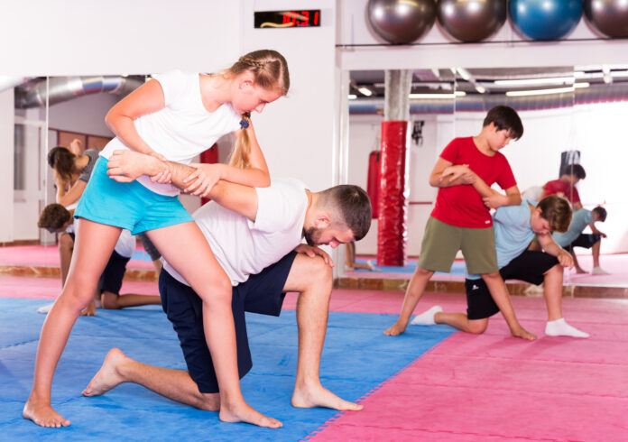 Kids with adults practicing effective techniques of self-defence in training room