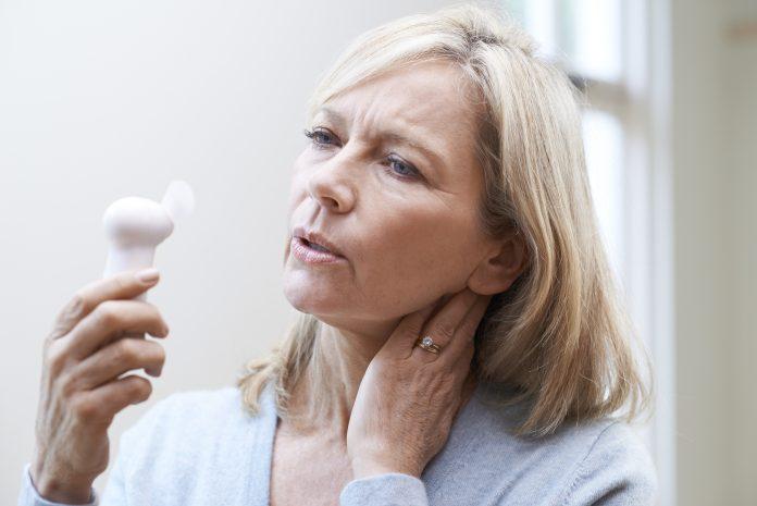 Femme d'âge mûr subissant des bouffées de chaleur dues à la ménopause