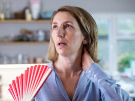 Mature Woman Experiencing Hot Flush From Menopause Using Fan