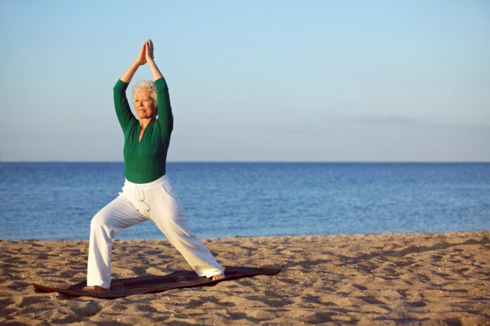 Mature woman stretching on the beach. Senior woman practicing yoga on the beach during morning