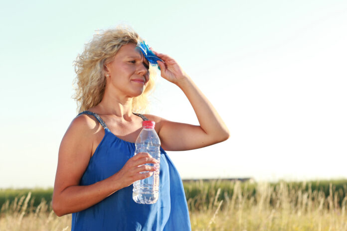 Mature woman with water bottle in summer heat