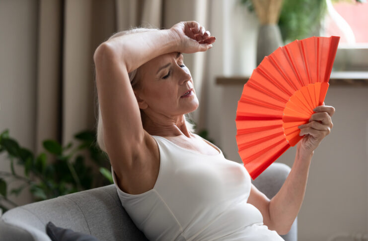 Middle-aged woman leaned on sofa resting in living room cools herself with orange colour hand fan touch forehead feels unwell suffers from unbearable hot summer weather at home without airconditioner