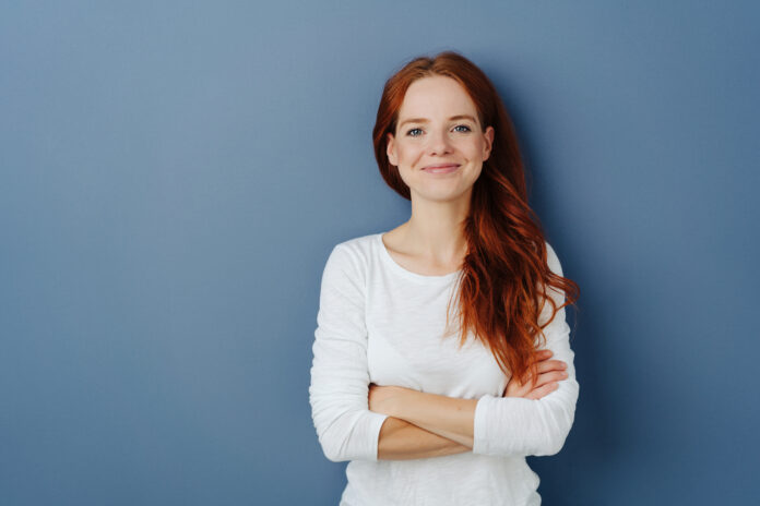 Pleased confident young redhead woman with a beaming smile and folded arms posing on a blue studio background with copy space grinning at the camera