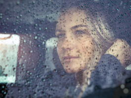 Portrait of a beautiful sad woman sitting in the car in rainy weather, pensive girl looking through the window glass with rain drops, autumn melancholy concept