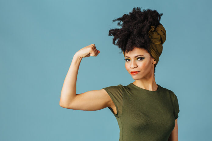 Portrait of a young woman showing her arm and strength