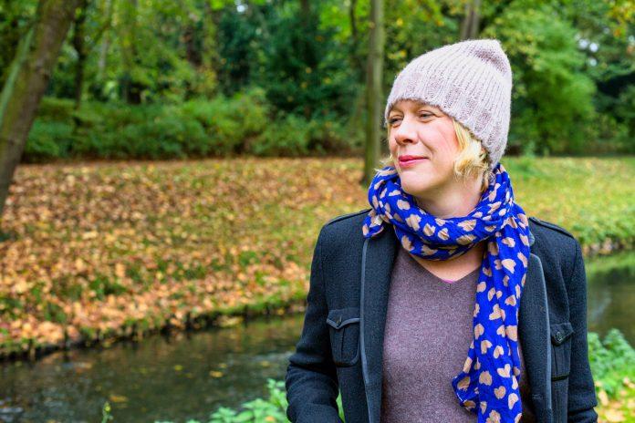 portrait d'une femme blonde d'une quarantaine d'années marchant dans un parc en automne