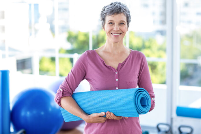 Portrait of mature woman with yoga mat while standing in fitness studio