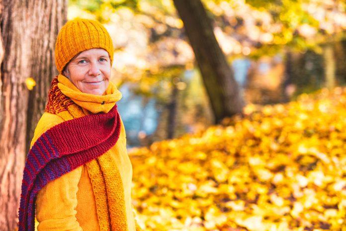 portrait of woman in her 50s walking in park in autumn
