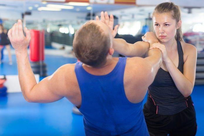 Positive Frau kämpft mit Trainer auf dem Selbstverteidigungskurs für Frauen im Sportverein