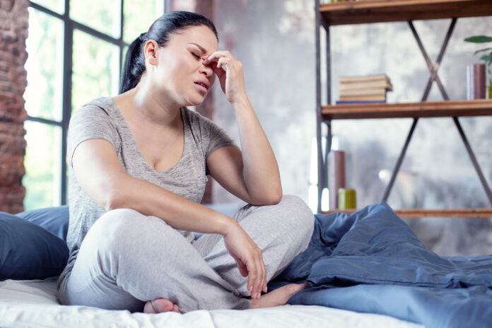 Rebound headache. Low angle of sorrowful emaciated woman staying on bed and massaging nose bridge