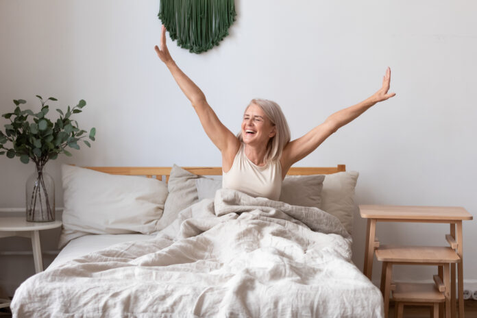 Refreshed elderly 50s female wakes up in morning stretches seated in bed in light bedroom at home, middle-aged woman feels happy and peppy after enough sleeping, greeting new day, good morning concept