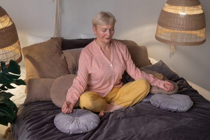 Femme âgée méditant en pratiquant le yoga à l'intérieur. Harmonie, pratique du yoga, équilibre, méditation, relaxation à la maison.
