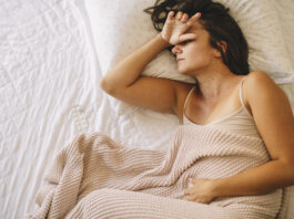 Sick young woman in bed. Woman have menstrual pain.