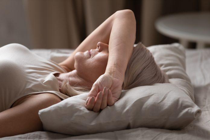 Vue de côté, plan rapproché d'une femme d'âge moyen allongée dans un lit à la maison ou à l'hôtel, couvrant ses yeux avec un bras, essayant de s'endormir la nuit ou se protégeant de la lumière du jour dérangeante le matin.