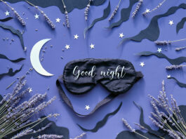Sleep mask with lavender on dark blue color background with black clouds, Moon and stars. Text Good night on the mask. Quality of sleep, aromatherapy, herbal remedies. Creative flat lay.