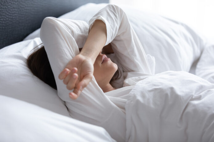 Sleepless young woman suffering from insomnia or nightmares close up, bad dreams, tired depressed female covering eyes with hands, lying on pillow in bed, feeling headache or migraine