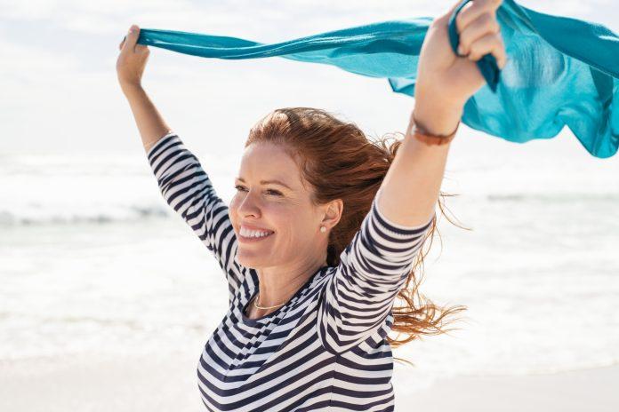 Lächelnde reife Frau hält blauen Schal über den Kopf beim Spaziergang am Strand. Glückliche aktive und gesunde Frau, die den Sommerurlaub am Meer genießt. Dame mittleren Alters in lässigen Laufen am Meer mit blauem Stoff.