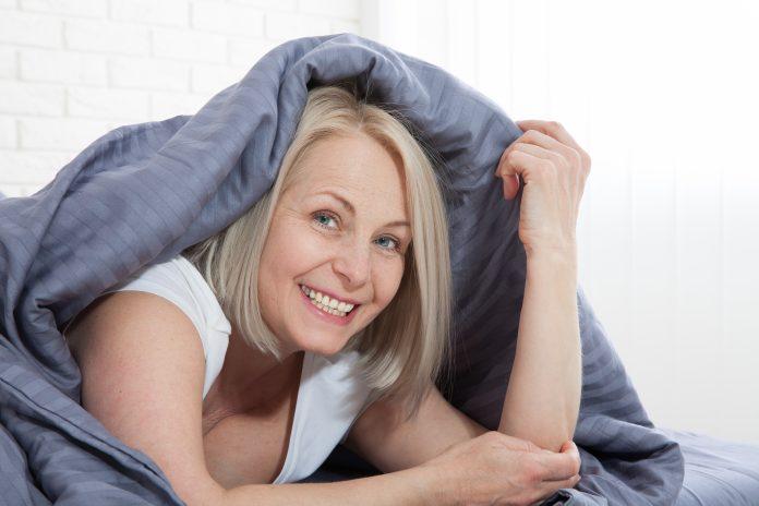 Femme souriante sous la couette dans sa chambre