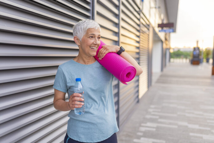 Smiling woman with yoga mat and water. Cheerful Woman Holding Rolled Up Exercise Mat. Fit, healthy and sporty woman in sportswear. Happy mature woman with a yoga mat