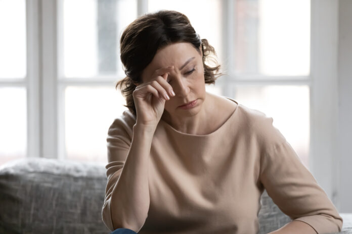 Stressed middle aged brown haired woman worrying about hard life situation, feeling unwell alone at home. Unhappy older lady mourning, suffering from negative thoughts or loneliness indoors.