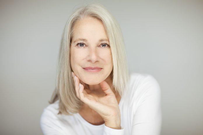 impresionante hermosa y segura de sí misma mejor mujer de edad con el pelo gris sonriendo a la cámara, retrato con fondo blanco