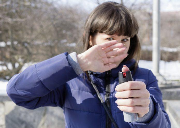 Tränengas oder Papper-Spray in der Hand einer jungen kaukasischen Frau, Mittel zur Selbstverteidigung in einem Wüstenpark. Nahaufnahme, selektiver Fokus.